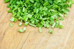 Siekać zielone cebule na drewnianej ciapanie desce Zdjęcie Stock