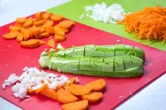 Siekający cebula, marchewka i zucchini na tle, zieleń i czerwień wsiadamy Zdjęcie Stock