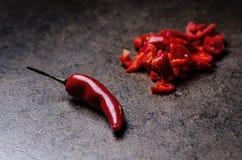 Siekający czerwony chili pieprz na czarnym tle Korzenny na drewnianej łyżce warzywo Pojęcie gorący jedzenie Zdjęcia Royalty Free