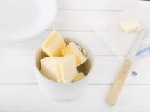 Siekający masło w białym pucharze na lekkim tle Obrazy Stock