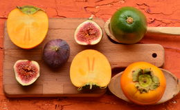 Siekający persimmon na ciapanie desce i figa Rocznika temat fotografia royalty free