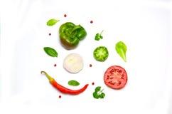 Siekający warzywa pomidory, cebuli chili, papryka, sałata i grochy na białym tle basilu i pieprzu zdjęcie royalty free