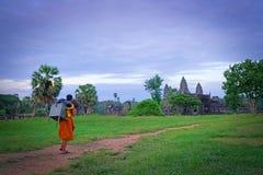 SIEM OOGST, KAMBODJA - SEPTEMBER 21, 2018: Jonge monniks dragende bezittingen op zijn rug in het beroemde oriëntatiepunt Angkor W stock fotografie