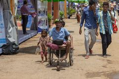 Siem Reap, Cambodia, 14 April 2018: Poor children and disabled beggar in chair on public market street.