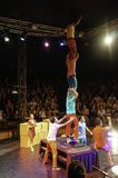 A acrobatics troupe is performing their shows, and there are lots of people watching and enjoying the show. stock photo
