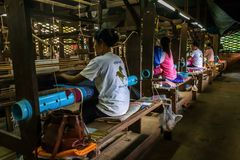 Women weave patterns with silk in Cambodia. SIEM REAP, CAMBODIA - AUGUST 24, 2015: Women weave decorative cloths with silks at a silk farm stock photography