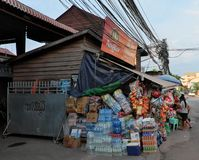 Huge number of boxes of all sorts of drinks and food near a small shop. Water bottles stock image