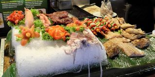 A large ice plate on which vegetables, meat, fish and octopuses lie, street food royalty free stock photos