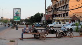 Several men sit on a cart. Direct city street on which motor transport goes. City life. Siem Reap, Cambodia, December 17, 2018 several men sit on a cart. Direct stock photography