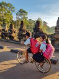 Two cambodian children in uniforms. Siem Reap, Cambodia - DECEMBER 29, 2017: Two cambodian children in uniforms going to school by bike Royalty Free Stock Images
