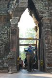 Tourists pass the south gate of Angkor Thom on an elephant royalty free stock image