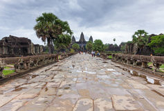 Siem Reap, Cambodia - 25 June, 2014: The walkway to Angkor Wat Temple in an overcast day on June 25, 2014, Siem Reap, Cambodia. The walkway to Angkor Wat Temple royalty free stock photos