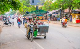Siem Reap, Cambodia - 31 March 2018: Seller on a motorcycle in the city street. Mobile eatery on bike. Food stall on motorbike. Street eatery on wheels. Low Royalty Free Stock Photo