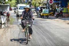 Siem Reap, Cambodia, March 19, 2016: A woman riding a bicycle on Royalty Free Stock Photography