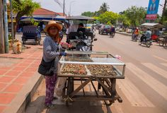 Siem Reap, Cambodia - 30 March, 2018: Woman selling fast food on street. Fastfood on asian street. Seafood snack seller. Streetfood in Cambodia. Shells fried Stock Image