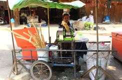 Woman is squeezing sugar cane juice royalty free stock photography