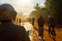 Bicycles and motorbikes on a dirt road in Cambodia royalty free stock image