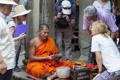 Siem Reap Cambodja - 14 April 2018: Kambodjansk läs- mantra för buddistisk munk för turist i den Angkor Wat templet royaltyfri foto