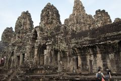 Siem Reap Cambodja December 31 2017, turister framme av gallerit med baslättnader på Bayon Wat en 12th århundradetempel inom Arkivbild