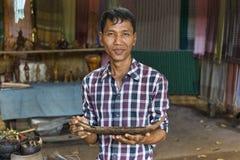 Siem Reap Cambodja - Januari 03, 2017: En hantverkare på byn för gömma i handflatansockerproducenter som visar en av hans träarbe Royaltyfria Bilder
