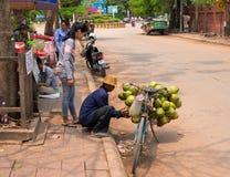 Siem Reap Cambodja - 30 mars, 2018: Kokosnötsäljare på cykeln Enkelt jobb som säljer cocomuttrar royaltyfri foto