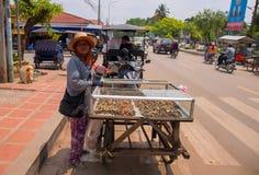 Siem Reap Cambodja - 30 mars, 2018: Kvinna som säljer snabbmat på gatan Fastfood på den asiatiska gatan Fotografering för Bildbyråer