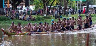 SIEM REAP CAMBODJA - NOVEMBER 2016: Det smala kambodjanska tävlings- fartyget med det fulla laget balanserade och ordnar till för Arkivbild