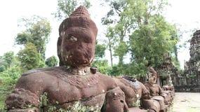 Siem Reap Cambodja November 15, 2017: Ingång som fodras med stenskulpturer till den Preah Khan templet arkivfoton