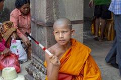 Siem Reap, Camboja - 25 de março de 2018: Monges budistas na roupa alaranjada no templo de Angkor Wat Menino budista que chanting fotos de stock royalty free