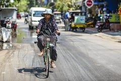 Siem Reap, Camboja, o 19 de março de 2016: Uma mulher que monta uma bicicleta sobre Fotografia de Stock Royalty Free