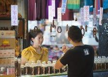 Siem Reap shopping - turisten köper träarmbandet Royaltyfri Foto