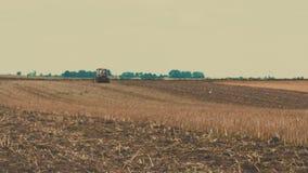 Siembra del tractor agrícola y campo de la cultivación metrajes