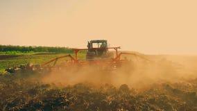 Siembra del tractor agrícola y campo de la cultivación Tractor con un remolque de la paleta que ara el campo después de puesta de metrajes