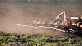 Siembra del tractor agrícola y campo de la cultivación Tractor con un remolque de la paleta que ara el campo después de puesta de almacen de video