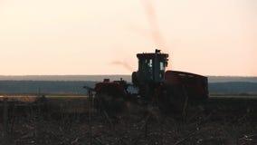 Siembra del tractor agrícola y campo de la cultivación Tractor que trabaja en el campo en la puesta del sol almacen de video