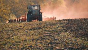 Siembra del tractor agrícola y campo de la cultivación Tractor que trabaja en el campo en la puesta del sol metrajes