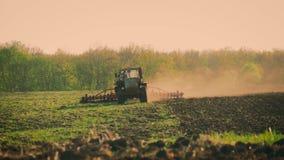Siembra del tractor agrícola y campo de la cultivación Tractor que trabaja en el campo en la puesta del sol almacen de metraje de vídeo