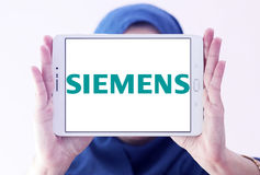 Siemens logo. Logo of german electronics company siemens on samsung tablet holded by arab muslim woman Stock Images