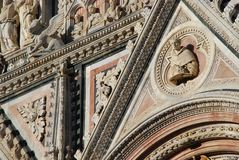 Siena Cathedral, building, carving, stone carving, arch. Siena Cathedral is building, arch and place of worship. That marvel has carving, basilica and facade and Royalty Free Stock Photos