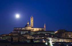 Siena cityscape by night and full moon Stock Images