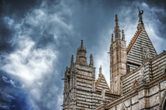 Siena Duomo under a dramatic sky seen from behind Stock Image