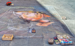 Siena, Italy - August 18, 2013: Street artist painting on asphalt chalk portrait of a girl. . Street art. Siena, Italy - August 18, 2013: Talent street artist royalty free stock photography