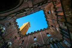 Siena landmark photo. Cortile del Podesta and Mangia tower. Tusc Royalty Free Stock Photos