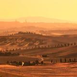 Siena, Rolling Hills auf Sonnenuntergang. Ländliche Landschaft mit Zypressenbäumen. Toskana, Italien Lizenzfreie Stockfotos