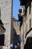 Siena, Tuscany, Italy. A view of a backstreet of Siena, showing old brick buildings and flags.  Sun, shadows and blue sky Royalty Free Stock Photos