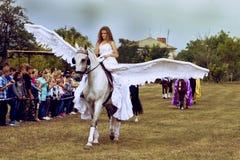 Sierpień 28, 2017: Dziewczyna z białymi aniołów skrzydłami jedzie konia przy wyścigi konny wydarzeniem w Ukraina, Odessa region S Fotografia Royalty Free