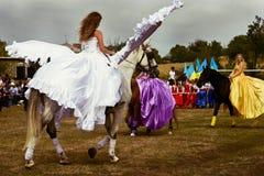 Sierpień 28, 2017: Dziewczyna z białymi aniołów skrzydłami jedzie konia wśród innych dziewczyn w pięknych długich sukniach przy w Obraz Stock