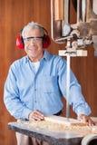 Sierra de cinta feliz de Cutting Wood With del carpintero Imagenes de archivo