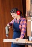 Sierra de cinta femenina de Drilling Wood In del carpintero imagenes de archivo