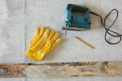 Sierra eléctrica de la plantilla y guantes amarillos fotografía de archivo